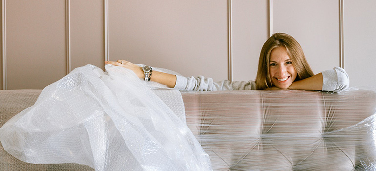 A girl smiling behind a couch that is wrapped in plastic sheets