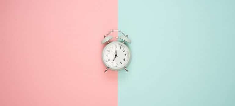Clock on a pink and blue surface.