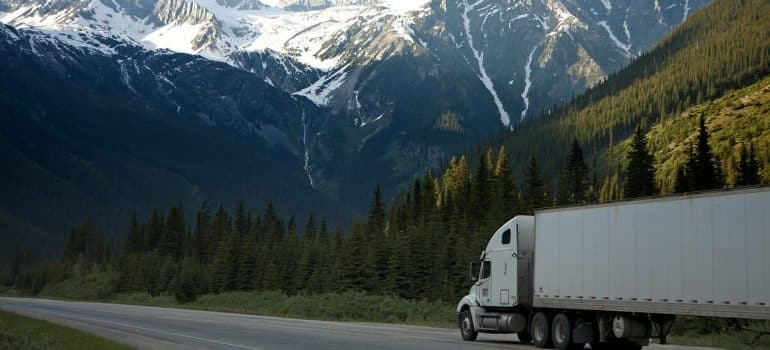 A truck on a freeway, near a forrest, beneath a mountain range
