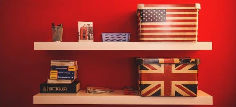 different boxes and books on two shelves on the wall