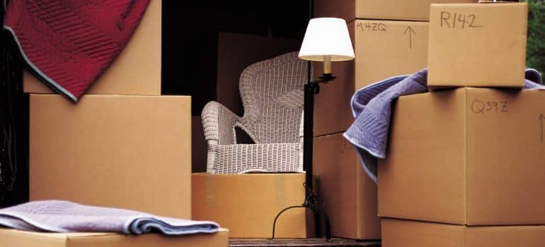 a stack of boxes with clothes sticking out and a lamp alongisde them