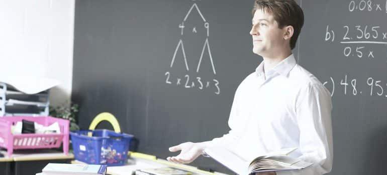 a teacher standing in front of a blackboard