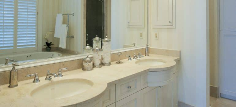 two sinks bellow a mirror and hygiene products on the counter
