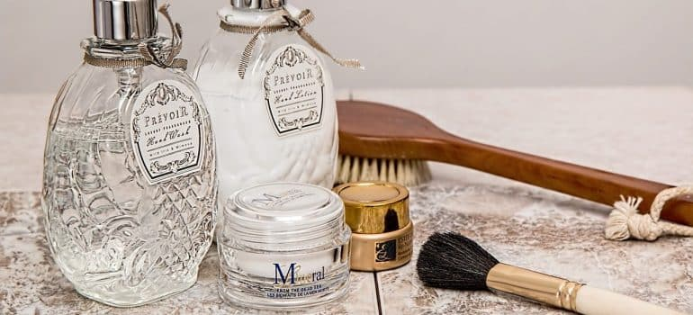 perfume water, a brush and make-up on the counter