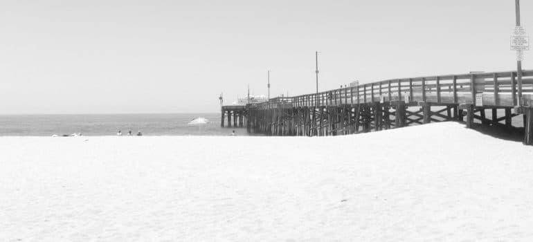 a sandy beach with a pier