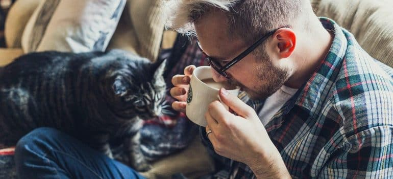 a man drinking a coffee with his cat by his side to ease settling into a new home after moving
