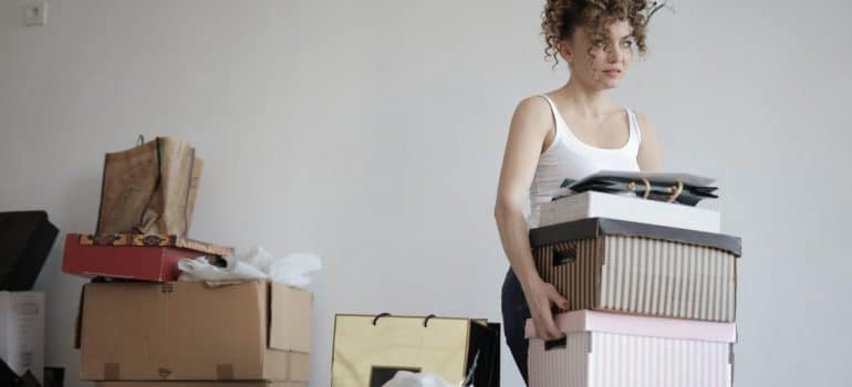 a woman moving boxes between rooms