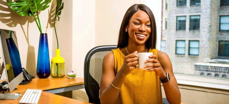 a woman in a yellow dress drinking coffee in her office