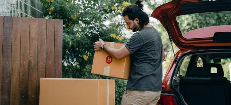 a man carrying cardboard boxes near his car to prepare them for the movers as one of our essential moving day tips