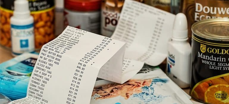 a reciept in front of different goods from the market
