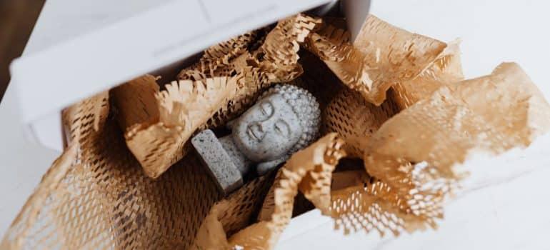 a cheramics statue of Buddha in a wrapping paper inside a shoe box