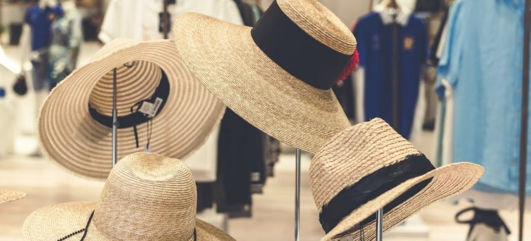 four straw hats on a store shelf