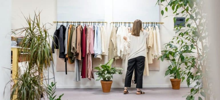 a woman going through her dresser to choose what to wear on moving day to California