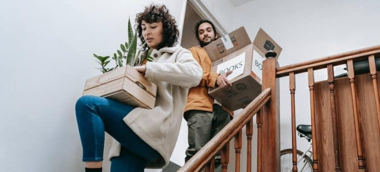 a couple carrying a box of items and a plant down the stairs