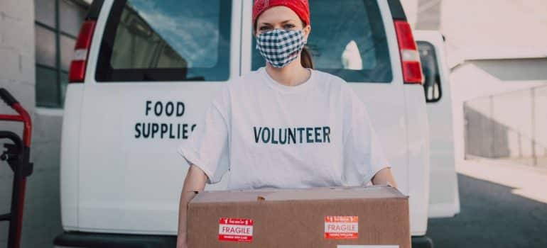 a woman volonteer holding a cardboard box infront of a white van