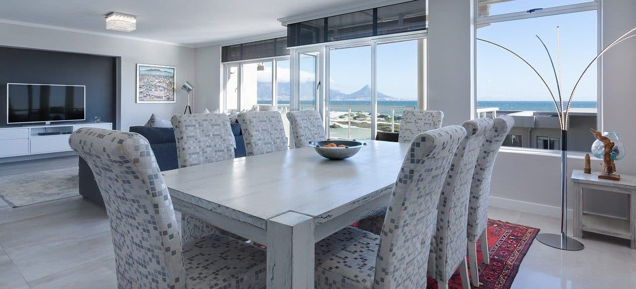 room with dining table and chairs, wall-mounted TV and sofa in front and one glass wall through which you can see the sea and the distant coast