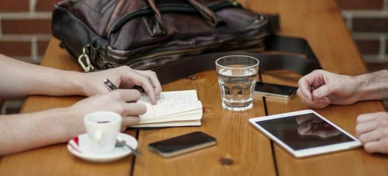 Two people sitting at a table with a notebook, tablet, mobile phones, a cup of coffee, a glass of water, a woman's bag and discuss