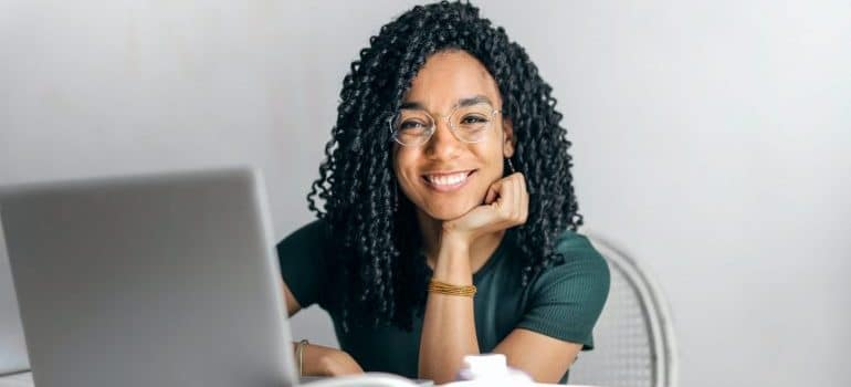 A woman in front of a computer searching for qualities to look for in a moving company