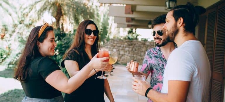 Two young women and two young men toast each other in front of the house when they meet new neighbors after moving to Villa Park