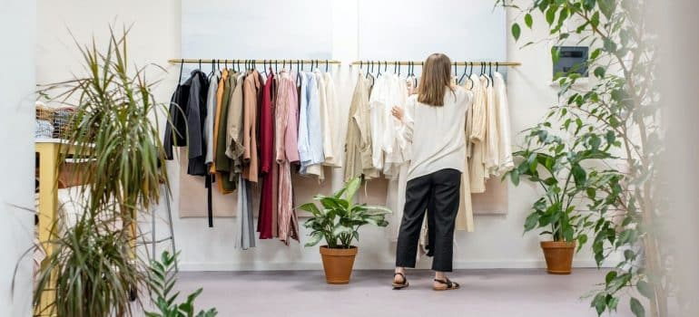 a woman in her wardrobe as a depicton of how to declutter your closet before moving