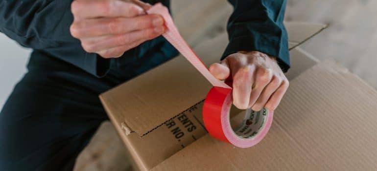 A man taping a moving box