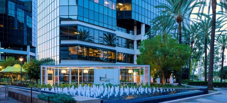 a building in glass with a fountain and palm trees in front with hot climate so you can leave your winter clothes when moving to Irvine
