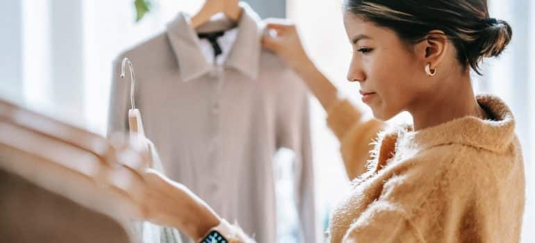 Woman in a sweater and with wristwatch is checking her shirts, to complete decluttering and get ready for relocation in a week