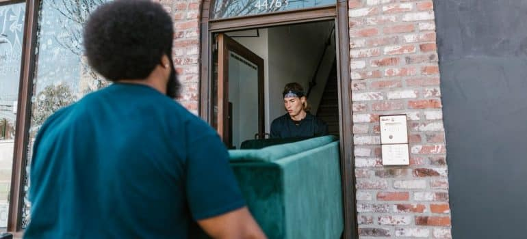 two men carrying a couch out of a home