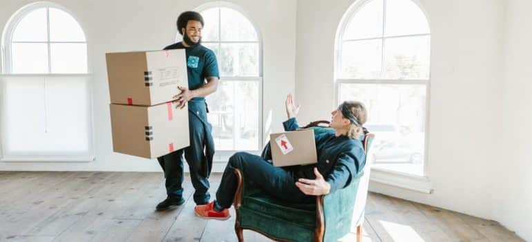two movers having fun in an empty room which depicts one of the risks of hiring amateur movers
