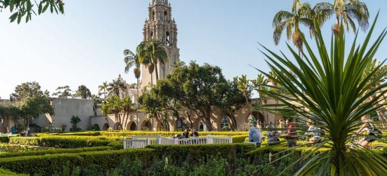 A green park with people, toll trees and old church, that people are visiting after moving from Orange County to San Diego