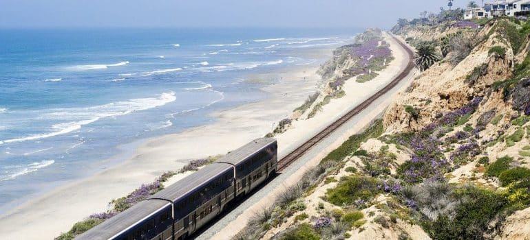 A train driving on the railroad, placed between the sandy beach and dunes, with the ocean and sky at the left.