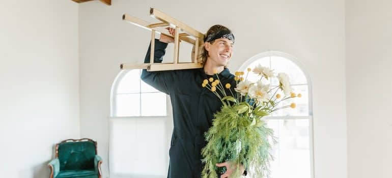 a man holding a stool and plants