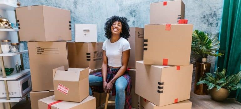 A girl sitting in the middle of cardboard boxes and smiling.