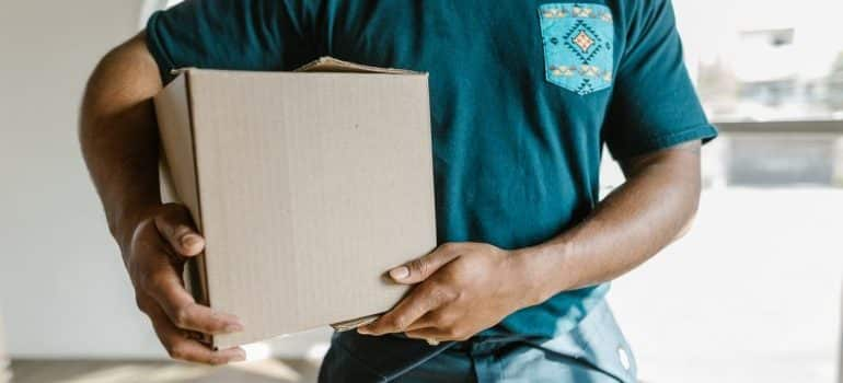 A worker in a moving company holding a cardboard box.