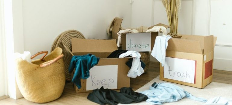 Boxes with different labeling and clothes on the floor.