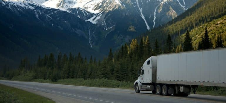 Moving truck on the reoad with nice view behind.