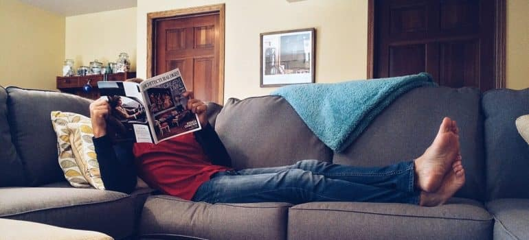 a man laying on the couch reading a magazine