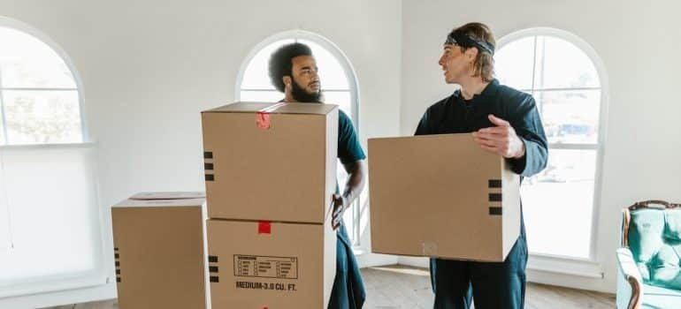 Workers of a moving comapny holding cardboard boxes for the move.