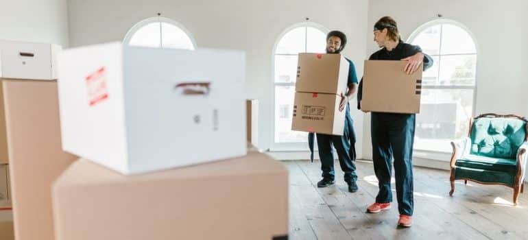 Movers holding cardboard boxes.